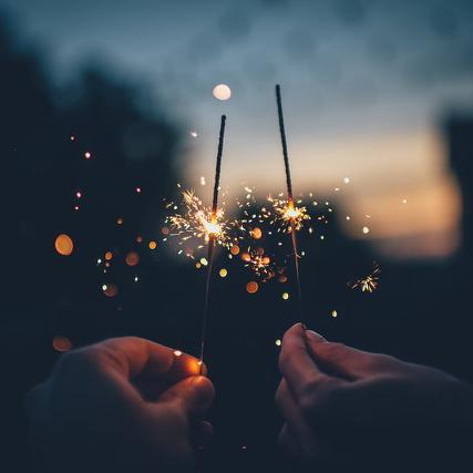 Die Hände zweier Personen die funkelnde Wunderkerzen in den blauen Nachthimmel halten.